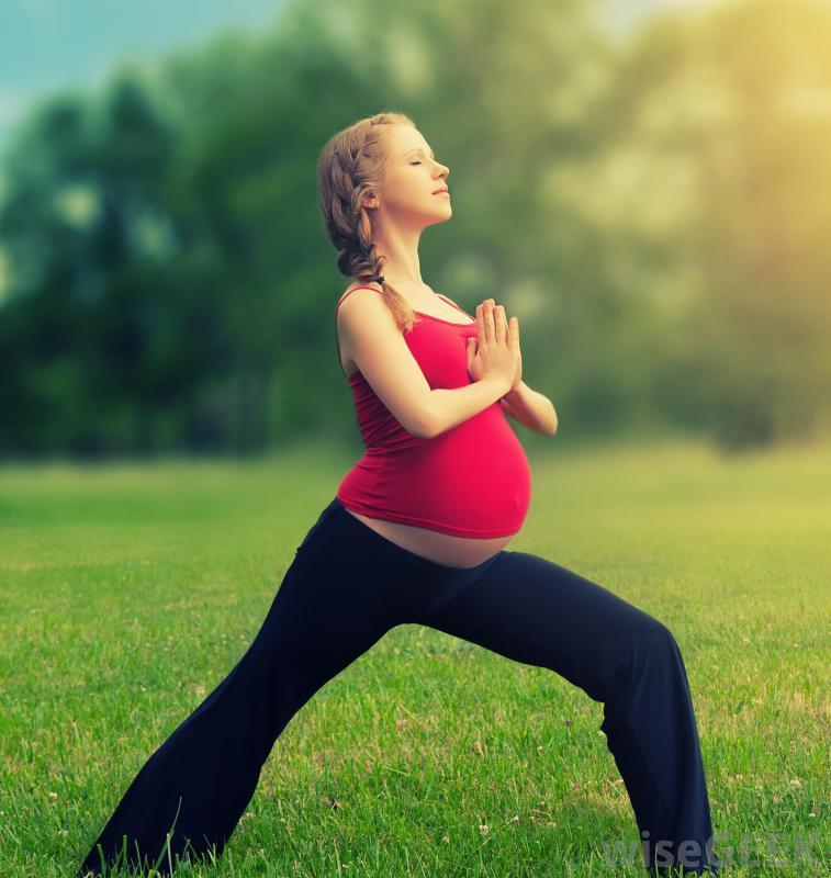 pregnant woman doing yoga outside