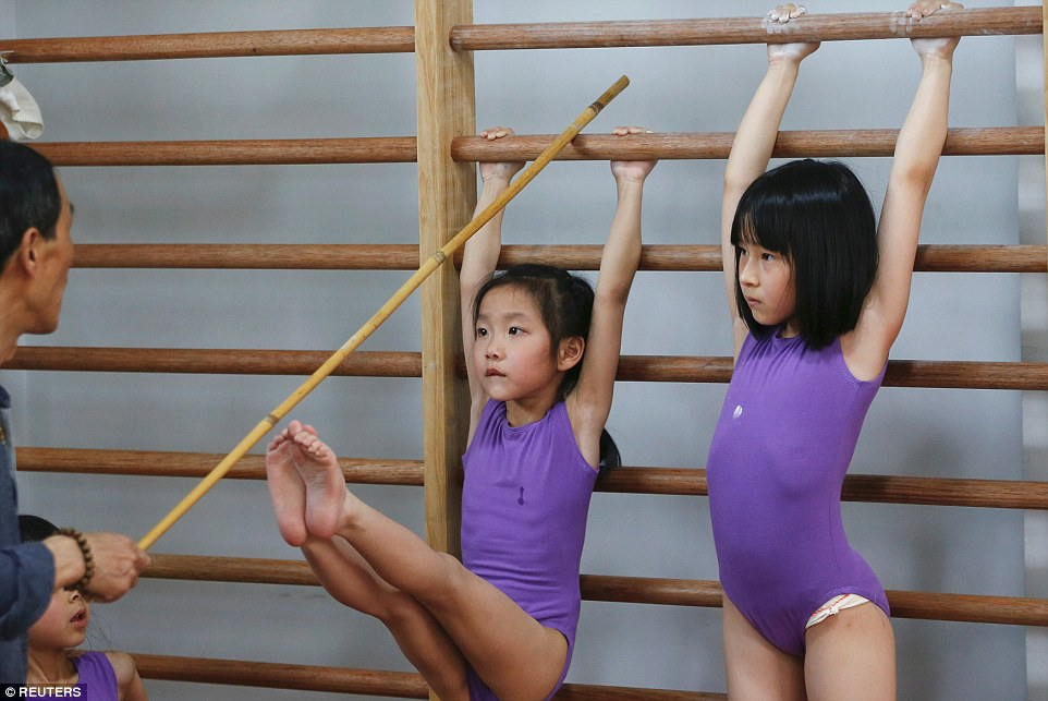 345C2BEE00000578 0 A girl tries to stretch her legs and reach a stick held by her c a 85 1463621392481