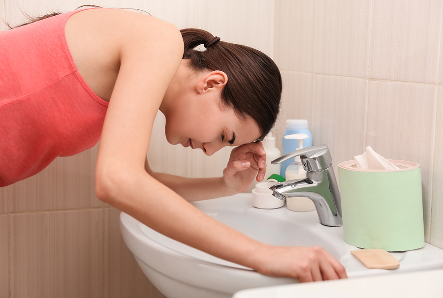 Young vomiting woman near sink 176243056