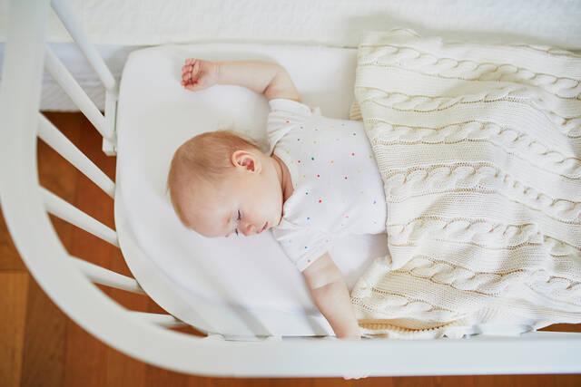 bigstock Baby Sleeping In Co sleeper Cr 335259748