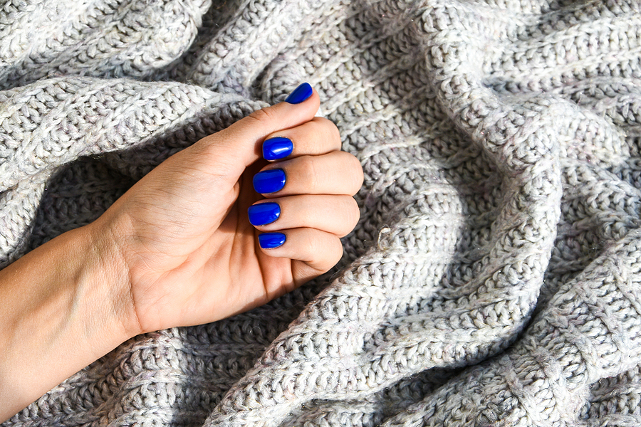 bigstock Hand With Blue Nails On Sweate 398504048