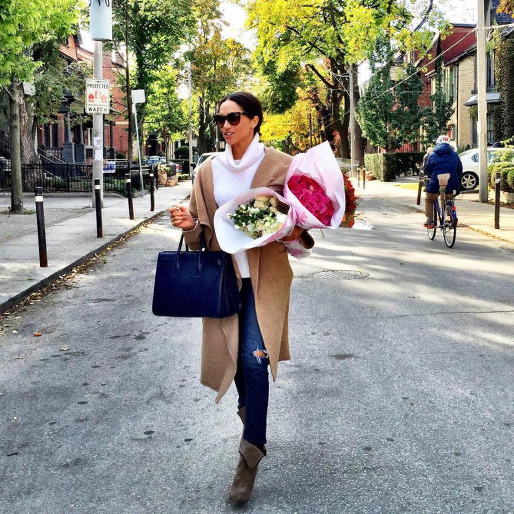 Η Meghan φορώντας ένα καμηλό παλτό και λευκό πουλόβερ, κρατώντας ανθοδέσμες στα χέρια της!