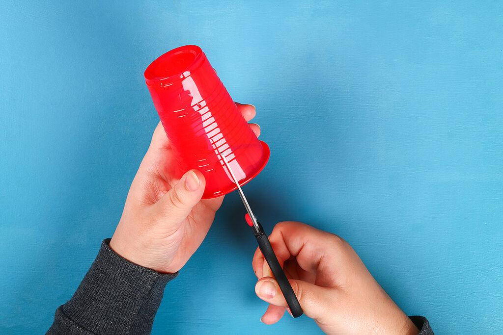 Παίρνουμε ένα πλαστικό ποτήρι ( εδώ είναι κόκκινο) και αρχίζουμε να το κόβουμε από πάνω προς τα κάτω σε λωρίδες