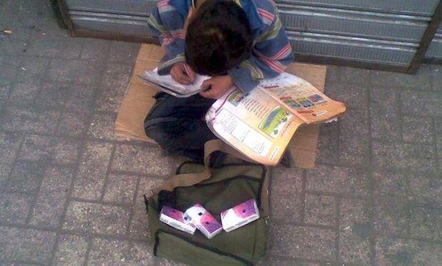 Παιδάκι πουλάει χαρτομάντιλα και διαβάζει (φωτογραφία)
