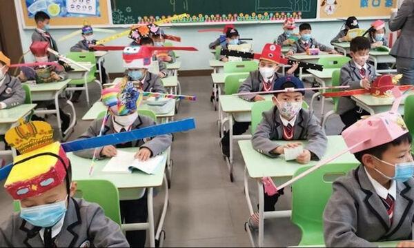 Παιδιά στη Χανγκτσόου φορούν καπέλα κοινωνικής αποστασιοποίησης με το που επιστρέφουν στο σχολείο