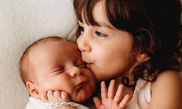 Παιδιά ποζάρουν στον φωτογραφικό φακό με το νεογέννητο αδερφάκι τους