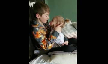 Αγόρι κρατά αγκαλιά την μικρή του αδελφή και της τραγουδά για να την παρηγορήσει